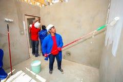 Diversi membri della comunità che dipingono una casa di basso costo a Soweto Immagine Stock