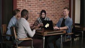 Diversi millennials facendo uso dei computer portatili e degli smartphones che si siedono nel luogo di lavoro, intrattenere di la archivi video