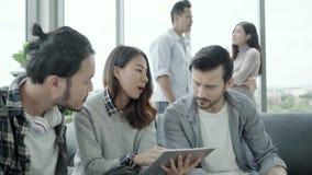 A diversidade criativa multi-étnico da equipe de jovens agrupa a equipe que guarda copos de café e que discute o encontro das ide