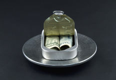 Diversification. Dollar and yen currency are rolled together into an open sardine can in a reflection of a new, basic diversification of investments stock photo