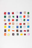 Diversifikation. 7 x 7 different polymer granulates in different colors on white in file Stock Photography