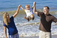 Diversión de la familia en la playa en el Sun Imagenes de archivo
