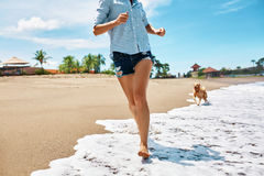 Diversión de la playa del verano Mujer que se ejecuta con el perro Vacaciones de los días de fiesta Verano Foto de archivo