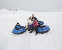 Diversión del invierno de la familia El Sledding y el jugar en nieve Imagenes de archivo