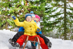 Diversión del invierno de los niños en el trineo que resbala abajo Foto de archivo libre de regalías