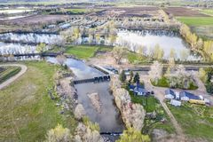 Diversion dam on a river at Colorado foothills. Diversion dam and irrigation canal on the Poudre RIver at Colorado foothills near Fort Collins, early spring stock photo