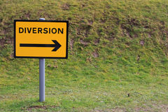 Diversion sign. A metal yellow and black diversion sign set against ad grass bank Stock Photo