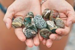 Diversità delle pietre marine in mani Fotografia Stock