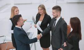 Diversiteits commercieel team die contract met handdruk in besluiten stock afbeeldingen