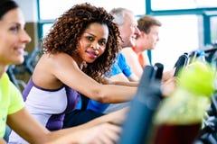 Diversiteitsgroep mensen op tredmolen in gymnastiek stock afbeeldingen