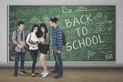 Diversiteitsstudenten met gekrabbel op het bord royalty-vrije stock afbeeldingen