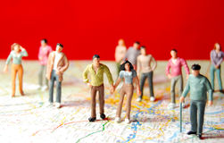 Diversity. Of miniature people travelling on map and red background royalty free stock photography
