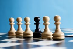 Diversity. Row of pawns, one black pawn stands out Stock Photos