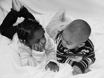 Diversity. A young boy and his twin sister lay on a sheet looking into each others eyes Royalty Free Stock Photo