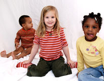 Diversity. Three young kids sitting together but all doing there own thing, showing diversity Stock Image