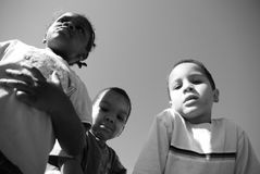 Diversity. Three children of mixed races standing together looking down at the camera Royalty Free Stock Photography