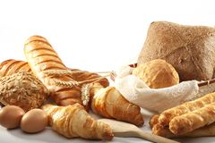 Diversity of bread and croissant, eggs, in a basket with linen c stock photo