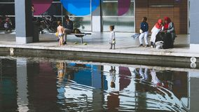 Diversity in Britain, Children Playing near Water with their Par Royalty Free Stock Photography
