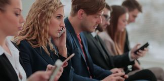 Businesspeople Using Technology In Busy Lobby Area Of Office stock images