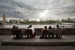 Diversity of families. Picture of indians and british people sitting on benches infront of a river in uk Stock Photos