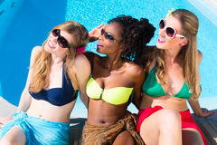 Diversity girls sitting on swimming pool in summer relaxing. African and Caucasian girls stock image