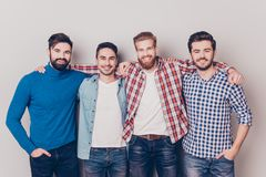 Diversity of men. Four cheerful young guys are standing and embracing, smiling, on pure background in casual outfit and jeans stock photos