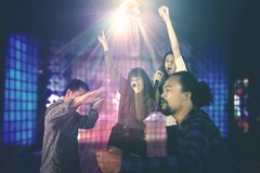 Diversity people dancing in the night club. Diverse people singing karaoke in the night club while dancing together under a disco ball with light rays Stock Photo