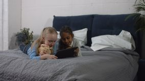 Diversity preteen girls playing tablet pc at home. Smiling diversity preteen girls playing digital tablet while lying on bed in the bedroom. Charming multiracial stock video