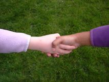 Diversity shake hand. Two diverse culture girls shaking their hands in friendship Royalty Free Stock Images