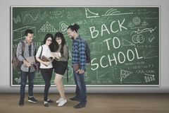 Diversity students with scribbles on the chalkboard Royalty Free Stock Images