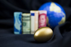 Diversity success in focus on gold nest egg with multiple curren Royalty Free Stock Photo