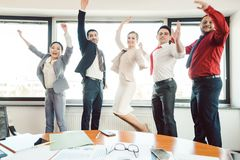 Diversity team of business people jumping high in the office stock images