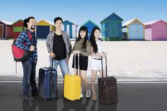 Diversity travelers near the cottage. Diversity travelers smiling at the camera while carrying suitcases and standing near the cottage on the beach Royalty Free Stock Photo