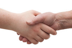 Diversity - young and old females shaking hands Royalty Free Stock Photography