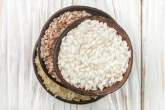 Diverso arroz crudo orgánico determinado en una tabla blanca de madera en de cerámica Foto de archivo