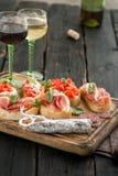 Diverso bruschetta italiano en el tablero de madera con el vino Foto de archivo
