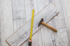 Diverso carpintero equipa el martillo de goma, ángulo del carpintero en el piso laminado fotografía de archivo