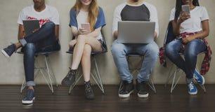 Diverso concetto della sedia del dispositivo di Digital dei giovani del gruppo fotografie stock libere da diritti