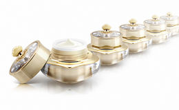 Diverso frasco cosmético da coroa dourada no branco Imagem de Stock Royalty Free
