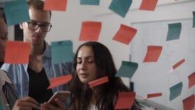 Diverso gruppo dei giovani positivi che sorridono mentre lavorando insieme durante il 'brainstorming' e stando dietro la parete d archivi video