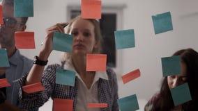 Diverso gruppo della gente di affari dei giovani mentre lavorando insieme durante il 'brainstorming' e stando dietro il vetro archivi video