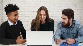 Diverso gruppo di giovani imprenditori che discutono affare facendo uso del computer portatile nell'ufficio Due uomini stanno dis stock footage