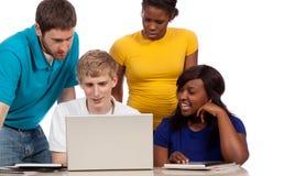 Diverso gruppo di studenti di college/amici che esaminano un computer Fotografia Stock Libera da Diritti