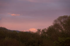 Diverso in nuvole di colore sopra le montagne Immagine Stock