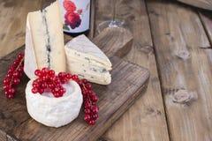 Diverso queso con el molde blanco y azul A del vino rojo y de las bayas frescas de la pasa roja Flores blancas El fondo de madera Foto de archivo