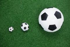 Diverso tamaño de fútboles en hierba artificial Fotografía de archivo