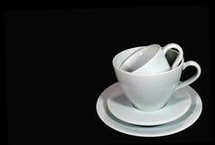 Diverso tamaño de las tazas de café blancas de la porcelana con los platillos llenados para arriba Imagen de archivo libre de regalías