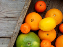 Diversos agrios en una caja de madera: mandarinas, naranjas, encanto, limón Visión desde arriba Imágenes de archivo libres de regalías