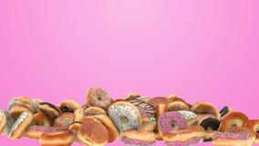 Diversos anillos de espuma que caen en un fondo rosado almacen de video