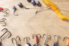 Diversos aparejos de pesca y gusano plástico en fondo del tablero de madera Imagen de archivo